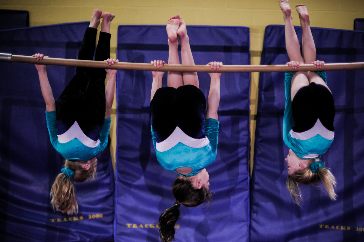three young gymnasts see the world upside down on the bar