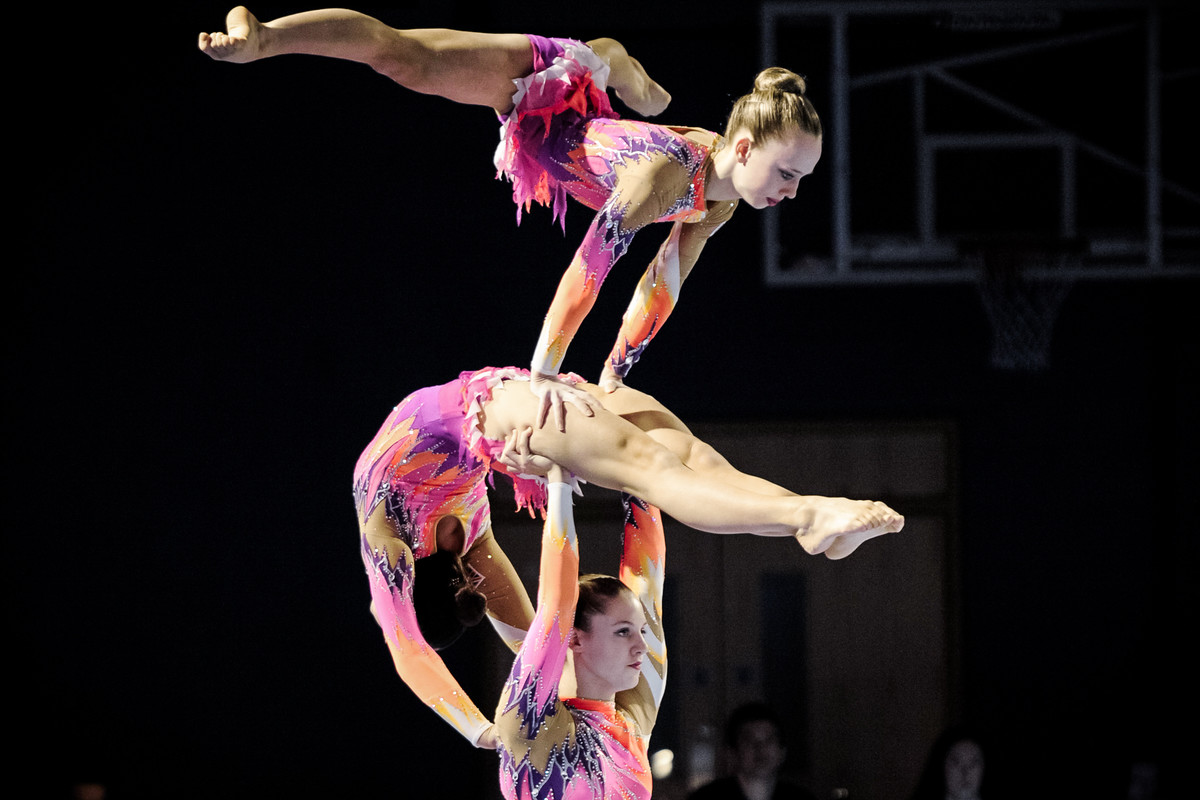 Trio of acrobatic gymnasts trio performing at competition
