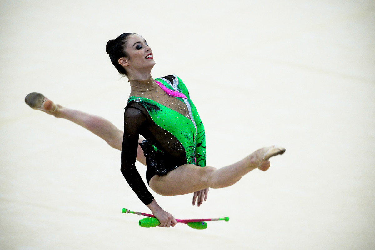 Laura Halford performs split leap with clubs