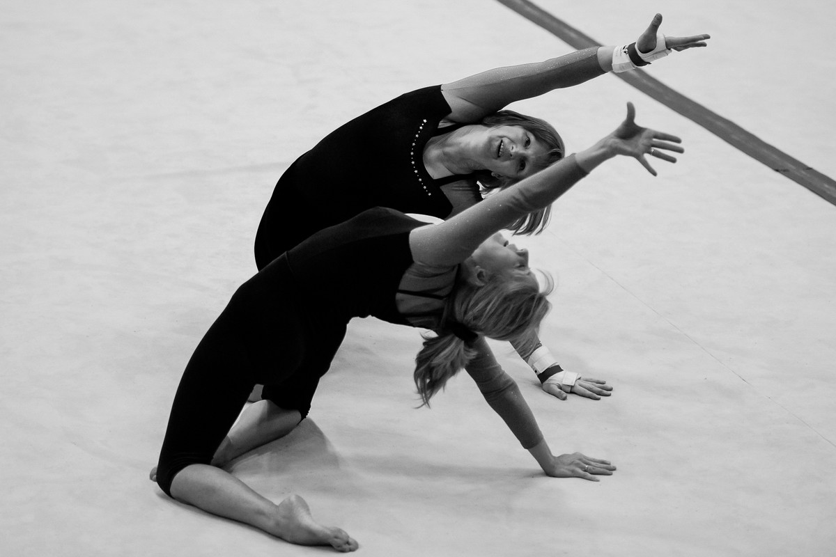 female adult gymnasts practice their routine
