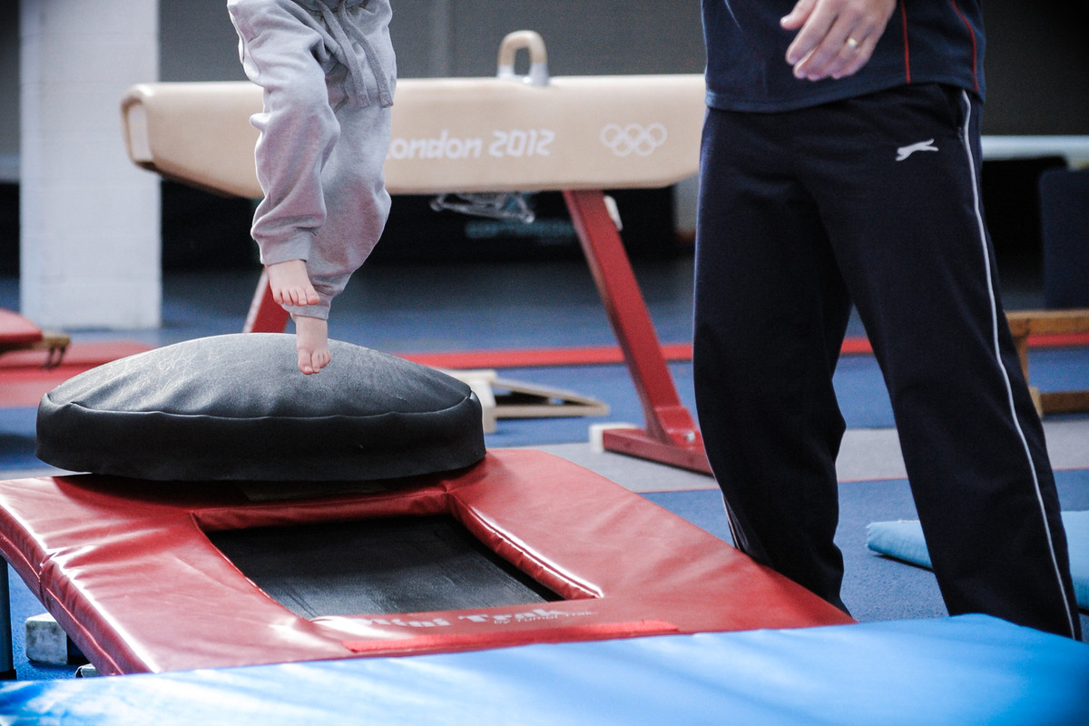 budding gymnast takes a leap supported by his coach