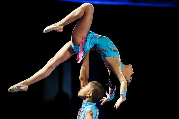 young acrobatic gymnast balances above her partner's head