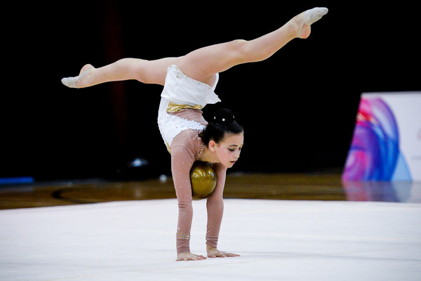 rhythmic gymnast performs handstand in splits balancing her ball