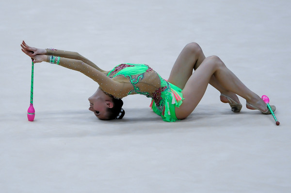 rhythmic gymnast performs with clubs