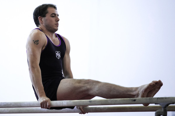 male adult gymnast takes on the parallel bars
