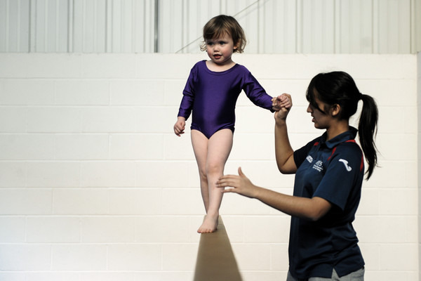 pre-school gymnast gets an early experience on the beam, developing balance and